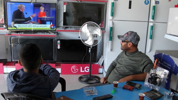 Two men in Gaza watch coverage of the election on November 9.