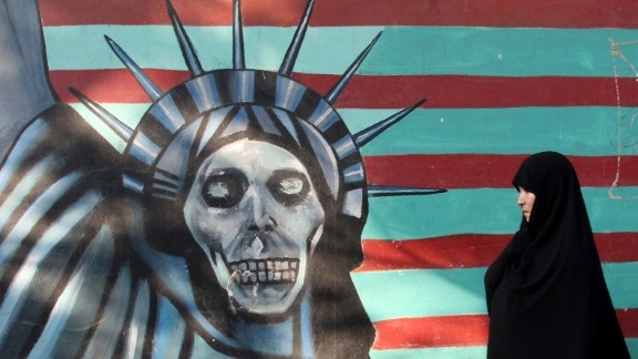 """An Iranian woman walks past a mural on the wall of the former US embassy in the Iranian capital Tehran on November 9, 2016. Iran's President Hassan Rouhani said there was """"no possibility"""" of its nuclear deal with world powers being overturned by US president-elect Donald Trump despite his threat to rip it up.   / AFP PHOTO / ATTA KENAREATTA KENARE/AFP/Getty Images"""