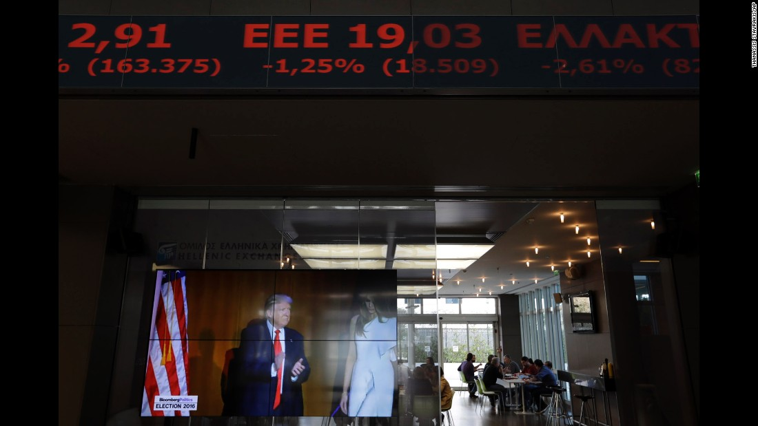 A stock ticker at the Athens Stock Exchange scrolls above a TV screen showing Trump on November 9.