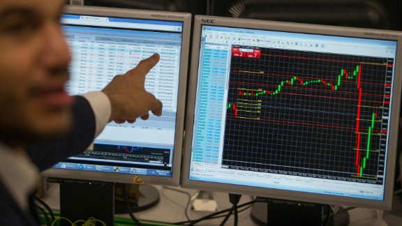 A stock trader at ETX Capital in London gestures to a screen showing the S&P 500 Index on November 9. Global stock markets dropped as Trump's victory became more likely on Election Day.