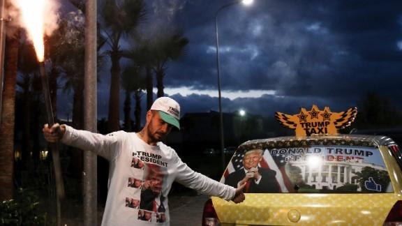Taxi driver Uljan Kolgjegja holds a flare as he celebrates Trump's victory in Tirana, Albania, on November 9.
