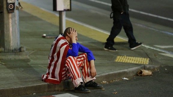 A man dressed in red-white-and-blue sits on the curb during a protest against President-elect Donald Trump, Wednesday, Nov. 9, 2016, in Seattle