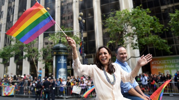 Kamala Harris waves a rainbow flag while participating in the San Francisco Pride parade in June.