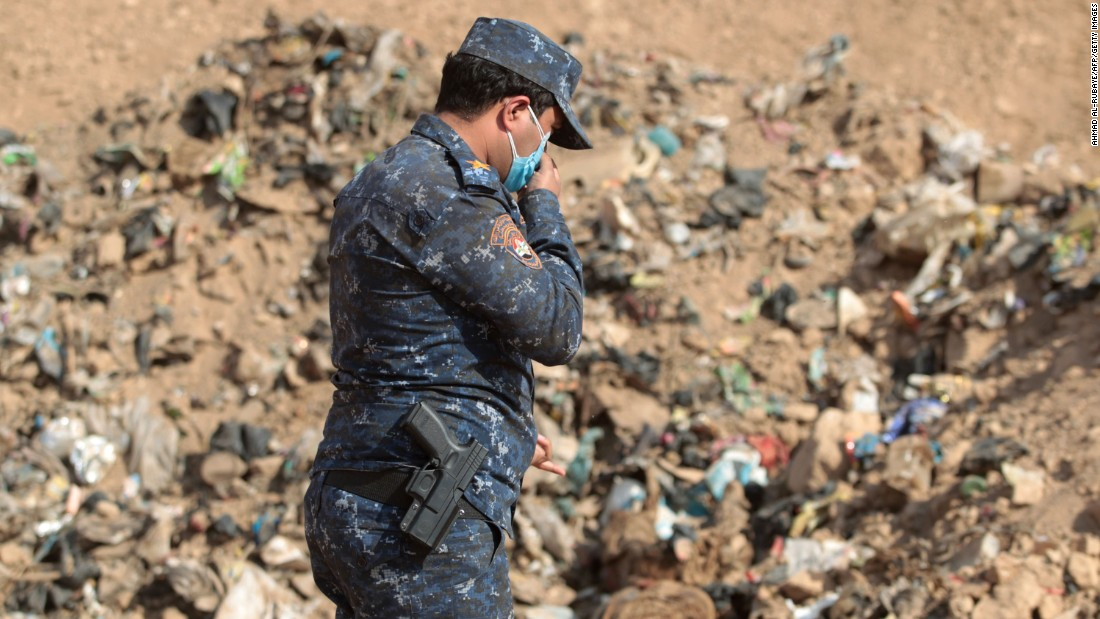 An Iraqi forces member investigates a mass grave that was discovered after coalition forces recaptured the area of Hamam al-Alil on Monday, November 7.