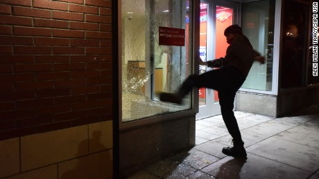 A protester kicks a bank's window during Thurdsay night's protest in Portland.