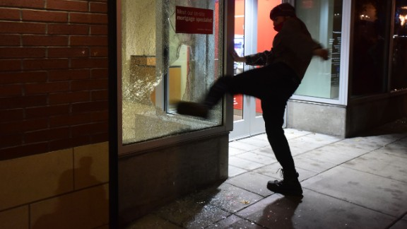 "A protester kicks the window of a Bank of America branch in Portland, Oregon, on November 10. What started out as a peaceful march with more than 4,000 people quickly turned violent. Portland police publicly declared a ""riot"" because of ""extensive criminal and dangerous behavior,"" according to posts on the department's Twitter page."
