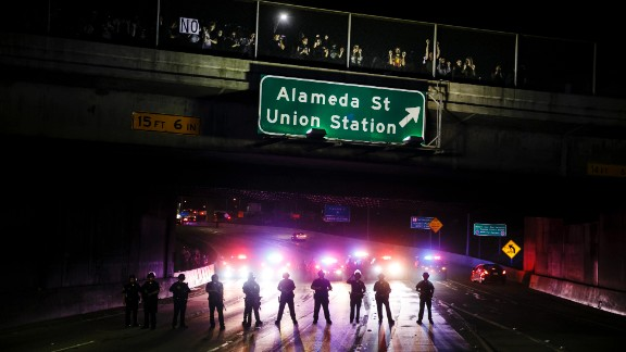 Police officers stand guard as they slowly clear Trump protesters from the 101 Freeway in Los Angeles on November 10.