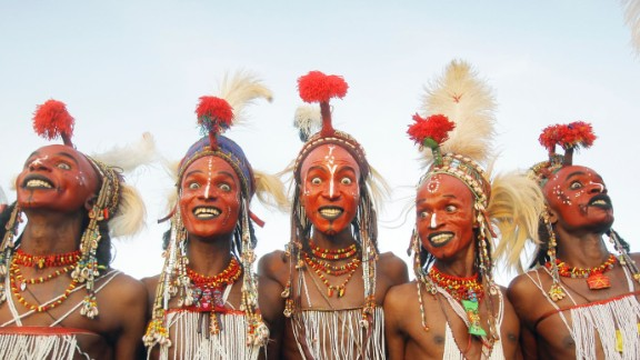"""At the end of the rainy season near Lake Chad, northern Niger, Wodaabe people come together for Cure Salee, the """"Festival of Nomads."""" At the center of celebrations is Gerewol, a male beauty contest and courtship ritual. Young men -- traditionally herdsmen -- wear full makeup, jewelry and their finest clothes and stand in line to await inspection by female onlookers. White teeth and white eyes are highly prized, so participants will grin broadly and pull all manner of expressions in the hope of attracting attention. It's flirtation en masse, in the hope of winning a night of passion with one of the judges."""