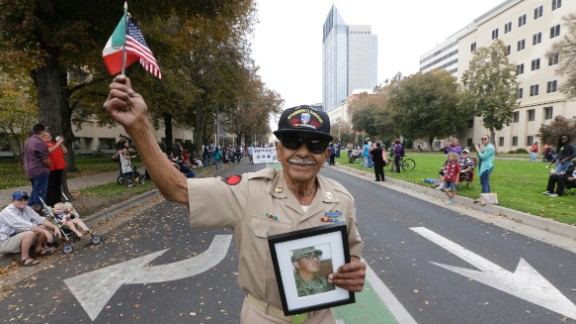 Korean War veteran Oscar Garcia marches during a Veterans Day parade in Sacramento, California, on November 11. He is holding a photo of his 18-year-old grandson, Daniel Garcia, who just graduated from Army boot camp.