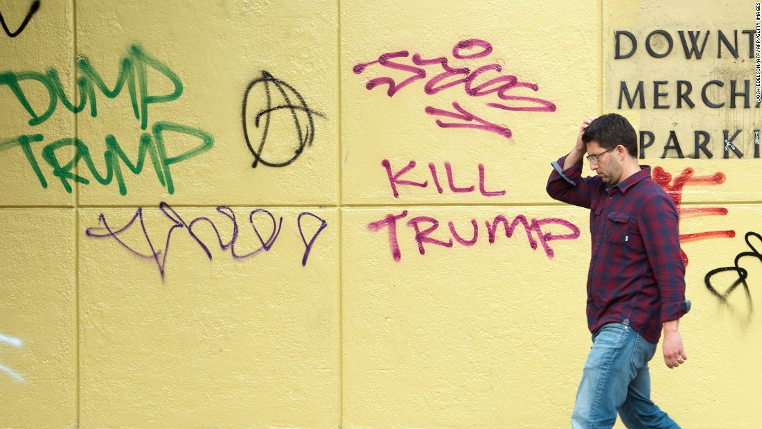 A man walks by anti-Trump graffiti in downtown Oakland, California, on November 11. Thousands of protesters have wreaked havoc on the city during anti-Trump marches, causing vandalism, fires and destruction of property.