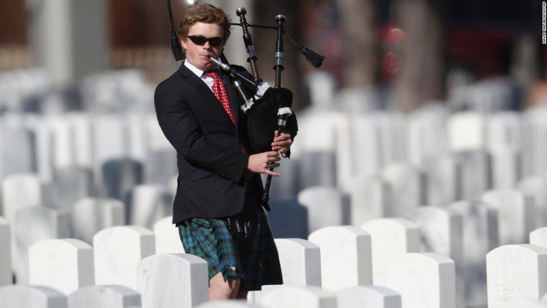 Sixteen-year-old Colin Lewis of Denver plays the bagpipes as he walks amid the headstones of veterans and their family members to mark Veterans Day in Fort Logan National Cemetery on November 11 in Sheridan, Colorado.