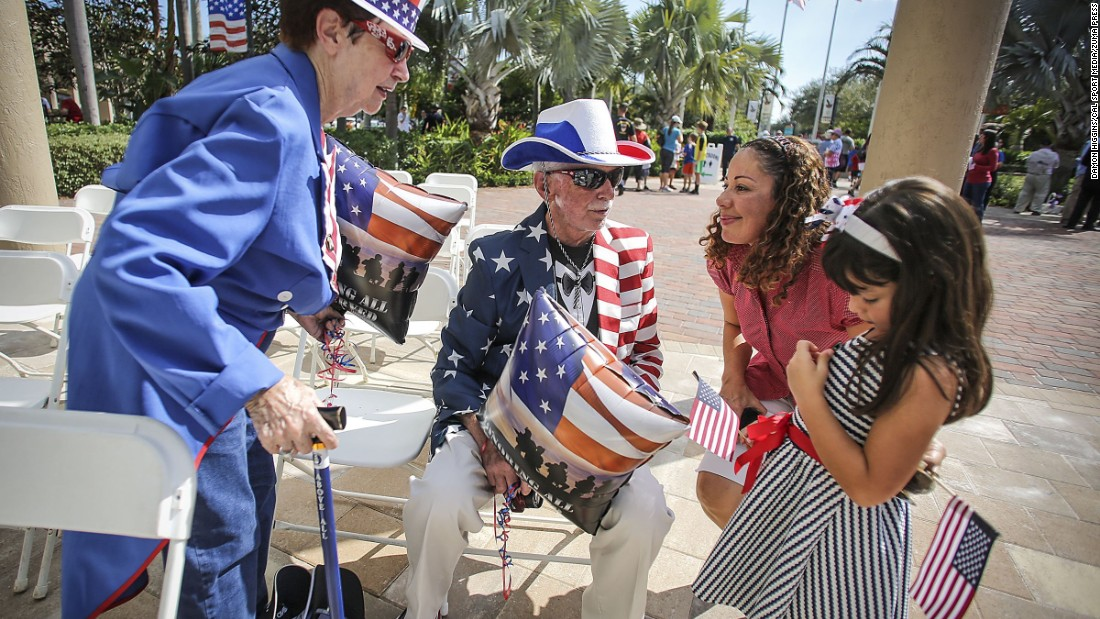 Retired air force veteran E. David Humphreys, 83, and his wife, Patricia, speak with  Ana Dunitz and her daughter Daniela, 5, after a Veterans Day ceremony at Veterans Plaza in Palm Beach Gardens, Florida.