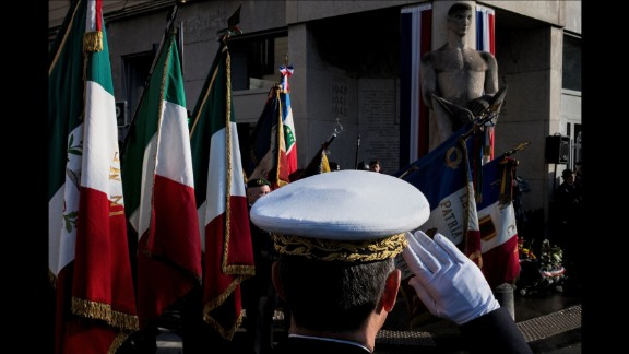 A French soldier salutes as veterans hold flags, on November 11 in Lyon, France.