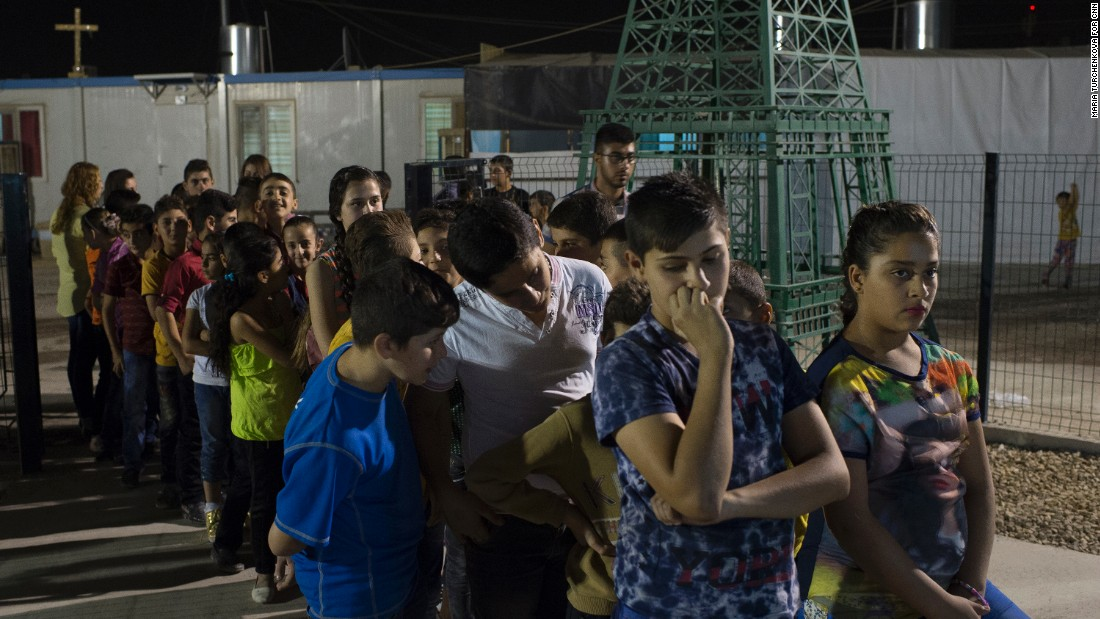 Young Iraqis wait for communion outside a church in<strong> </strong>Irbil's Ashti camp.