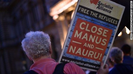 A protester holds a sign calling for the closure of offshore detention camps.