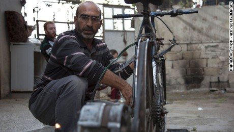 Syrian Abu Rahmo, a 48-year-old mechanic, welds a dynamo -- the small generator used to charge car batteries -- onto the back of an old bicycle in Aleppo's besieged Ansari neighbourhood on October 31, 2016.