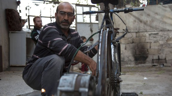 Syrian Abu Rahmo, a 48-year-old mechanic, welds a dynamo -- the small generator used to charge car batteries -- onto the back of an old bicycle in Aleppo