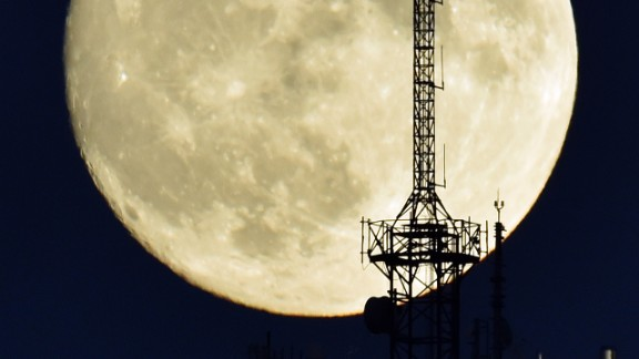 "The moon rises over a building in Madrid on November 13, 2016, on the eve of the ""supermoon."""