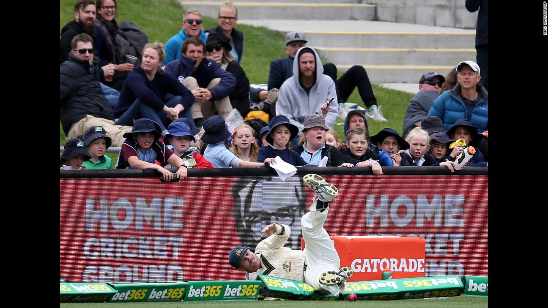 Australian cricket player David Warner crashes over the boundary rope while fielding a ball against South Africa in Hobart, Australia, on Monday, November 14.