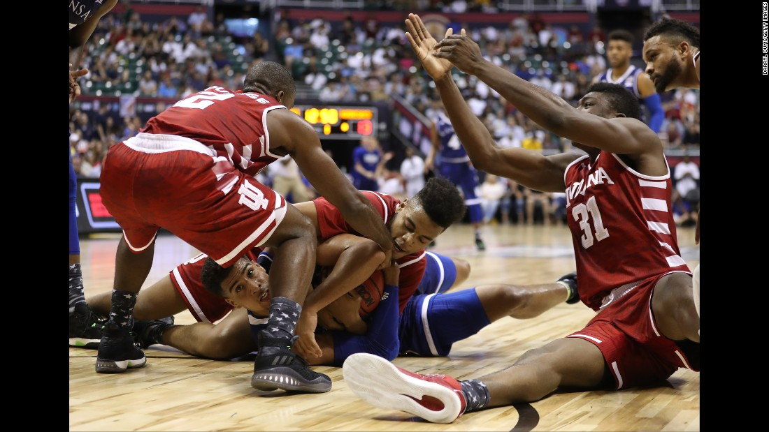 Kansas' Landen Lucas is mobbed by Indiana players as they compete for a loose ball on Friday, November 11.