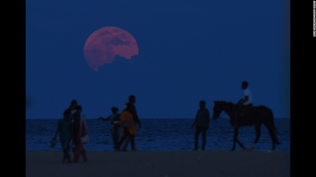A man rides a horse past people watching the supermoon in Chennai, India, on November 14.