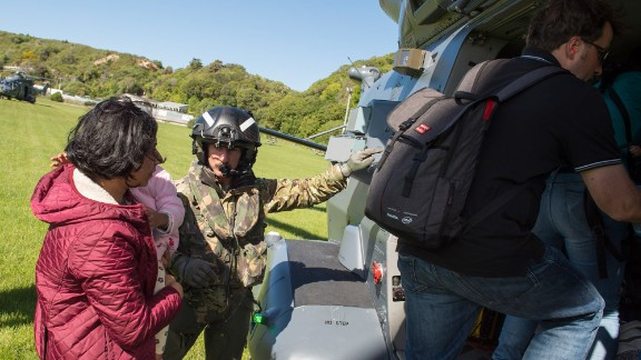 A member of the New Zealand Defence Force assists a family aboard a helicopter during evacuations of Kaikoura. The popular tourist destination on the South Island is home to more than 3,500 people.