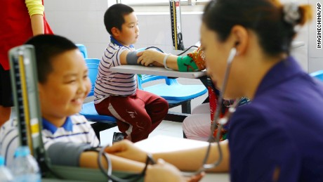 Chinese workers measure blood pressures of obese young students during a physical examination at a school in Shanghai, China, 27 May 2014.