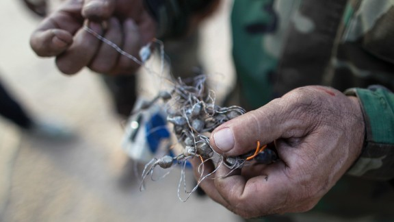 A Kurdish Peshmerga fighter holds part of a defused bomb planted by ISIS militants in Bashiqa, Iraq, on Friday, November 11.