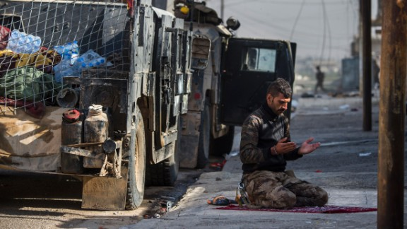 An Iraqi special forces soldier prays next to a Humvee before troops pushed toward Mosul