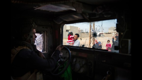 An Iraqi special forces soldier looks on as residents flee Mosul.
