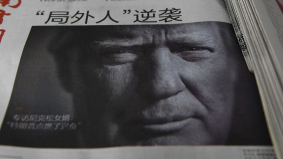 """A Chinese newspaper is on sale, with the headline that reads """"Outsider strikes back"""", featuring Donald Trump on the front page in Beijing on November 10, 2016. The American public on November 9 voted for the Republican candidate Donald Trump to be the 45th President of the United States.  / AFP / GREG BAKER        (Photo credit should read GREG BAKER/AFP/Getty Images)"""
