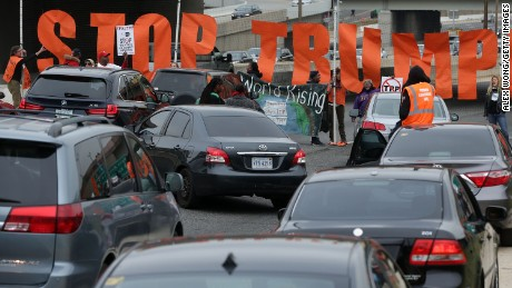 "Activists use a banner to block traffic on I-395 during an anti-Trump and anti-TPP protest November 14, 2016 in Washington, DC. Activists held a rally and a march ""to protest the Trans-Pacific Partnership and urge President-elect Donald Trump and members of Congress to reject the trade deal."""