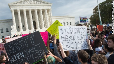Secondary school students holds signs in front of the Supreme Court in Washington, DC, on November 15, 2016 as they protest the election of US President-elect Donald Trump.