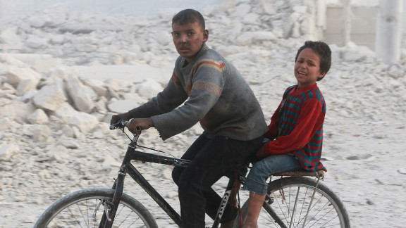 Children flee after airstrikes hit their neighborhood in eastern Aleppo on Tuesday.