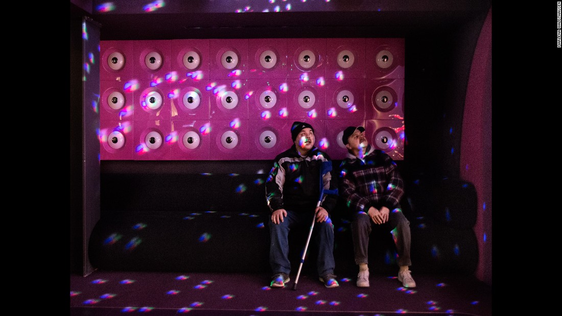 The twins are fascinated by light reflections at a museum's disco room.