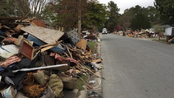 Weeks after Hurricane Matthew, debris piles in yards make it seem like the storm just hit Lumberton.
