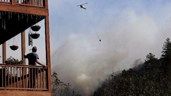 Eric Willey looks on from the porch of his home as a helicopter fights a wildfire in Tate City, Georgia, on Wednesday, November 16.