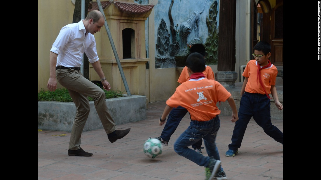 Britain's Prince William plays soccer with children as he visits a primary school in Hanoi, Vietnam, on Wednesday, November 16. He was in Vietnam to attend an international conference on wildlife trafficking.