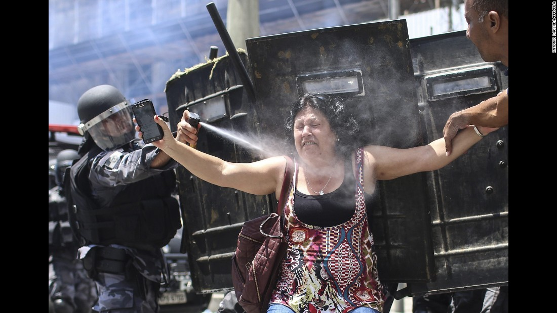 A police officer sprays a demonstrator during austerity protests in Rio de Janeiro on Wednesday, November 16.