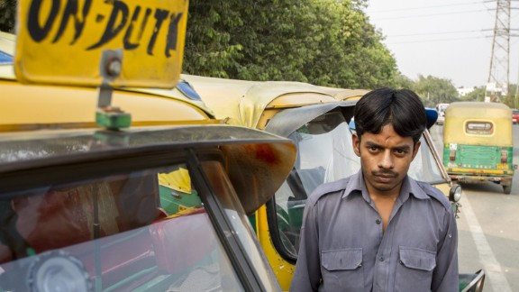 Sarvesh poses by his auto rickshaw.