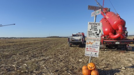 One of the air cannons that fires pumpkins is adorned with a humorous sign, in the whimsical spirit of Punkin Chunkin.
