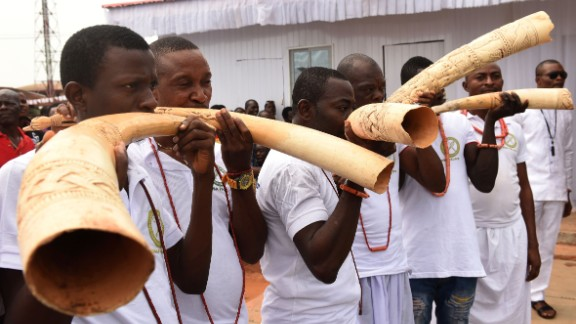 Royalist supporters blow in sculpt elephant tusks during the coronation ceremony.
