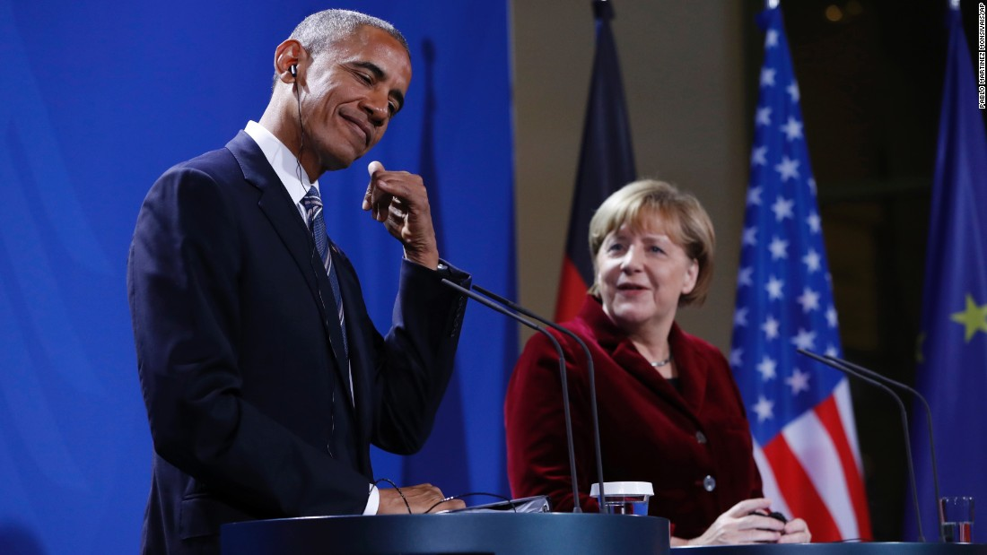 Obama acts like he's picking up a phone during his joint news conference with German Chancellor Angela Merkel in Berlin on Thursday, November 17.
