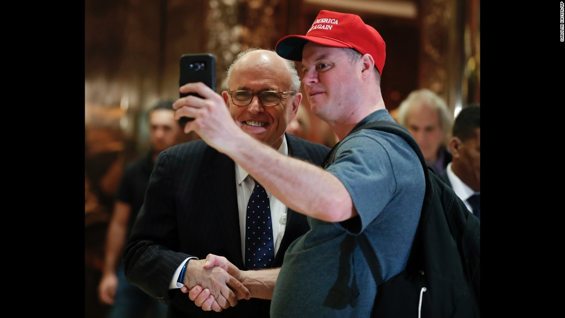 Former New York Mayor Rudy Giuliani poses with a Trump supporter at Trump Tower in New York on Wednesday, November 16.