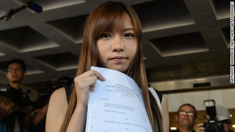Yau Wai-ching holds a court ruling as she leaves the High Court in Hong Kong on November 15, 2016.