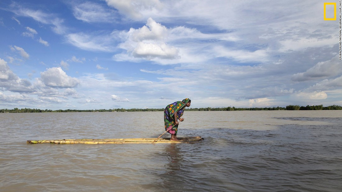 "Photo: Probal Rashid. ""A flood-affected woman on a raft approaches a boat, searching a dry place to shelter herself in Islampur, Jamalpur, Bangladesh. Bangladesh is one of the countries most vulnerable to the effects of climate change,"" wrote Rashid. <em>Via National Geographic Your Shot</em>"