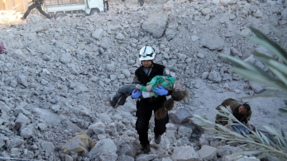 A man rescues a wounded child after an airstrike in Aleppo on November 18, 2016.
