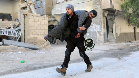 A White Helmets volunteer carries an injured man to safety on Saturday following an airstrike in eastern Aleppo.