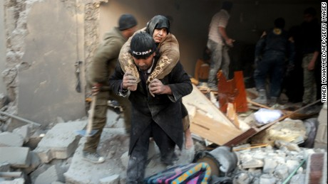 A Syrian rescuer carries a woman who was rescued from the rubble of a building following airstrikes on Aleppo's rebel-held district of al-Hamra on November 20, 2016.