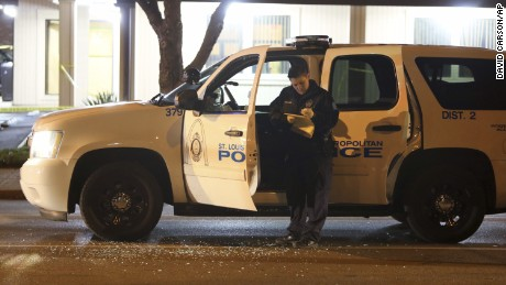 "Police investigate a scene after a St. Louis police officer was shot in what the police chief called an ""ambush"" on Sunday, Nov. 20, 2016, in St. Louis. Police Chief Sam Dotson said the 46-year-old officer was shot in the face. The suspect got away and a massive search was underway. (David Carson/St. Louis Post-Dispatch via AP)"